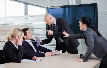 Business man threatning business partner, grabbing him by the tie at a meeting Stock Photo