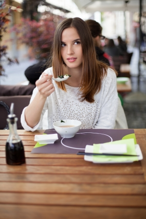 Pensive young woman eating soup in the restaurant photo