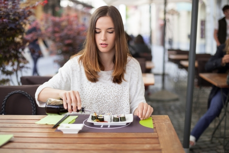 Young woman pouring soy sauce on sushi plate Stock Photo - 19754657