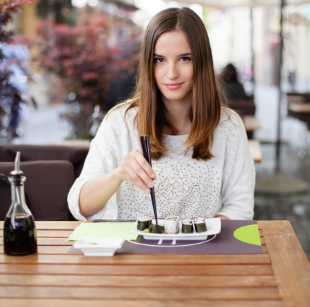 Young woman eating sushi in an Asian restaurant Stock Photo - 19754630