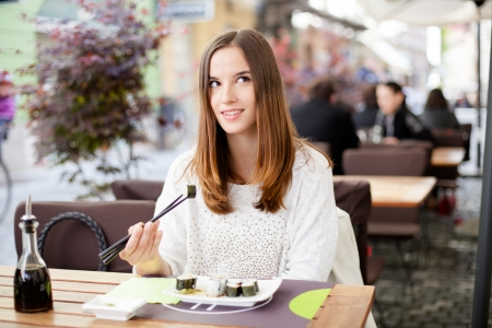 Young woman daydreaming while eating sushi Stock Photo - 19754644
