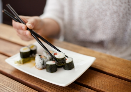 maki: Detailed view of a woman eating sushi