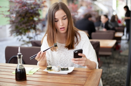 Young woman texting while eating sushi in a restaurant Stock Photo - 19754658
