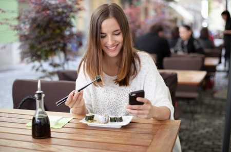 Happy young woman eating sushi in a restaurant and using mobile phone photo