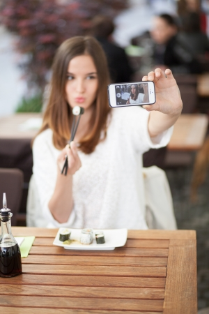 self: Young woman taking a self portrait in a sushi restaurant Stock Photo