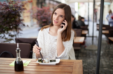 Beautiful young woman talking on the phone in a sushi restaurant Stock Photo - 19761490