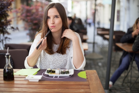 Young woman eating sushi in a restaurant Stock Photo - 19981015