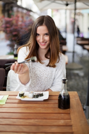 Young woman offering you sushi in a restaurant Stock Photo - 19981018