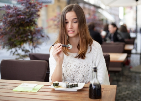 Young woman hesitant about eating sushi photo