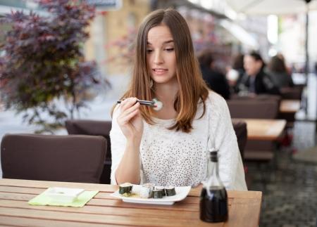 hesitant: Young woman hesitant about eating sushi Stock Photo