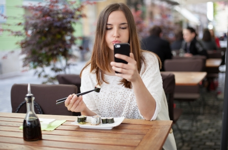 Young woman reading a message while eating sushi in a restaurant Stock Photo - 19980952