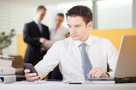 Businessman using mobile phone in an office photo