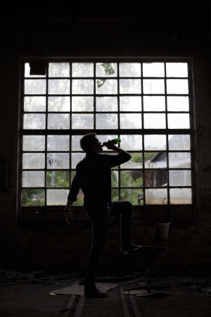 1 person: Young man drinking beer in a dark abandoned industrial building