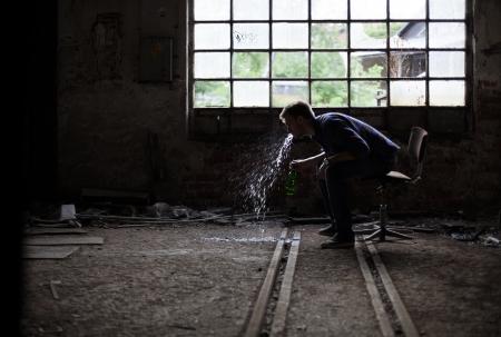 vomito: Drunk hombre vómitos joven en una nave industrial abandonada