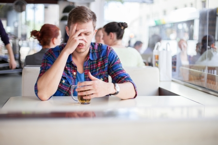addiction drinking: Young man drinking his problems away in a cafe
