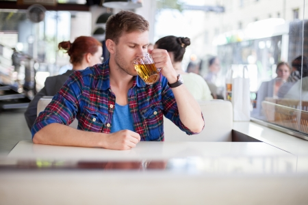 Young man drinking beer in a cafe photo