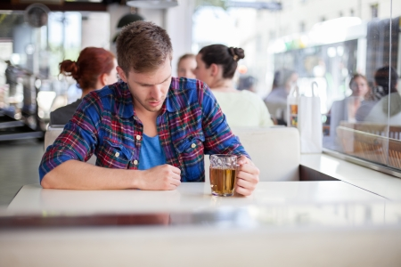 Depressed young man drinking beer in a bar photo