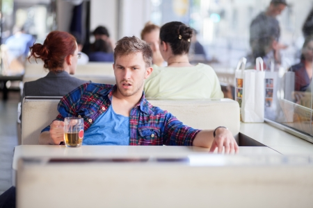 Drunk young man drinking beer in a cafe in the middle of the day photo