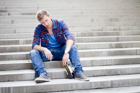 酒とたばこを飲んで階段に坐っている酔った人 写真素材