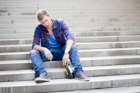 Drunk man sitting on the stairs drinking wine and smoking cigarette photo