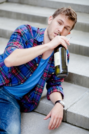 Drunk man drinking wine on the stairs and smoking cigarette photo