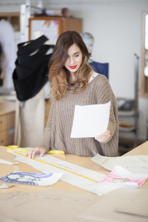 tailor measure: Fashion designer looking at dress design she drew Stock Photo