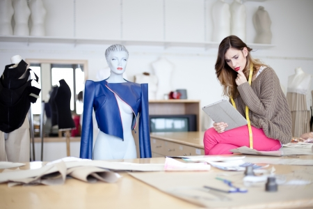 dressmaker: Fashion designer looking at designs on tablet computer. In the studio. Stock Photo