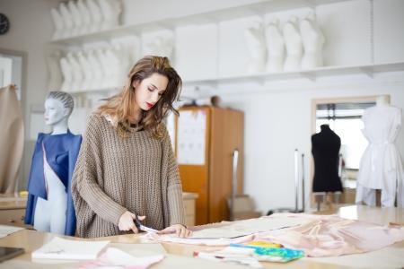 Fashion designer cutting fabric textile in a studio Stock Photo - 20285343