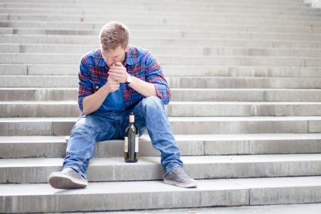 alcoholismo: Borracha del hombre joven enciende un cigarrillo en las escaleras Foto de archivo