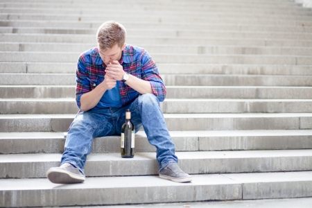 alcoholic beverages: Drunk young man lighting a cigarette on the stairs