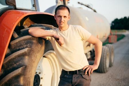 cisterna: Agricultores de pie junto al tractor y cisterna