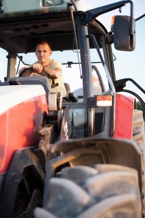 農家: 農夫は日の出で彼のトラクターに座っています。