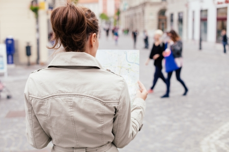 lost city: Woman looking at city map on the street  Looking for directions