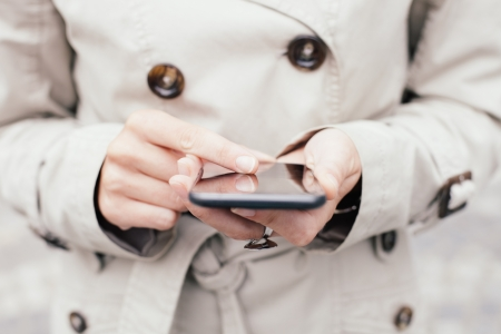 Woman wearing trench coat using smartphone photo