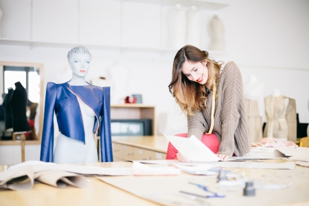 Fashion designer looking at sketches in studio photo