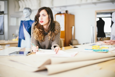 Pensive fashion designer drawing in studio photo