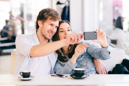 young couple: Couple taking photo of themselves with a phone in cafe Stock Photo
