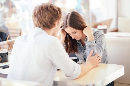 mujer llorando: Mujer joven llorando en Problemas de pareja café Foto de archivo