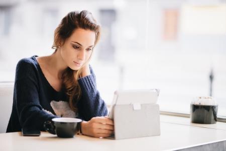 카페에서 태블릿 컴퓨터를 사용하는 젊은 여자 학생