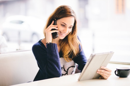using phone: Happy young woman talking on the phone in a cafe Stock Photo
