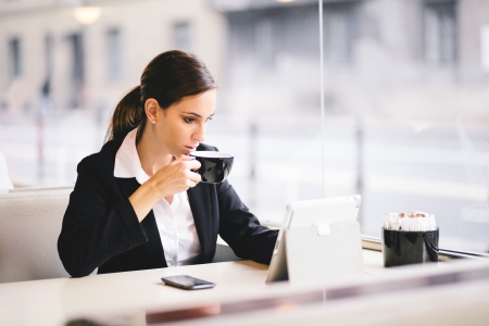 woman in cafe: Young businesswoman drinking coffee and using tablet computer in cafe Stock Photo