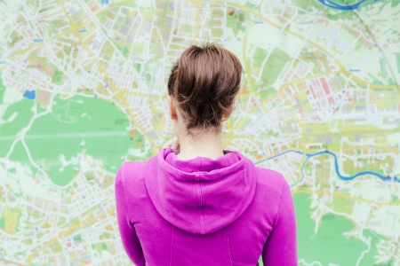 Young woman standing in front of tourist city map