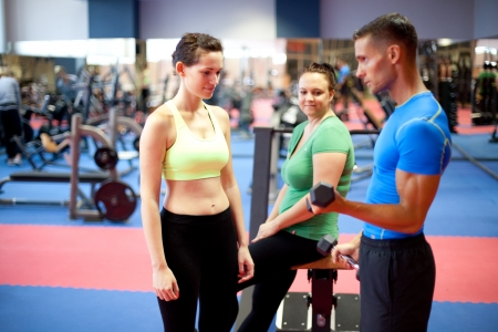 Personal trainer demonstrating a bicep exercise  At the gym  Selective focus  photo