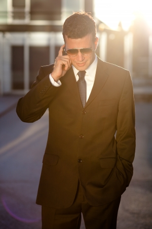Cool businessman taking a call in front of an office building photo