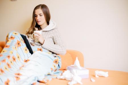 ragazza malata: Giovane donna con l'influenza fredda utilizzando il computer tablet sul divano