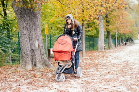 Young woman pushing her baby in stroller in a park photo