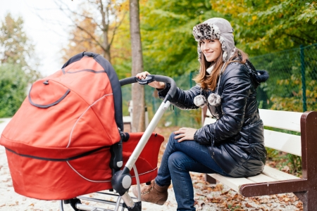 Young woman sitting on park bench with baby in stroller photo
