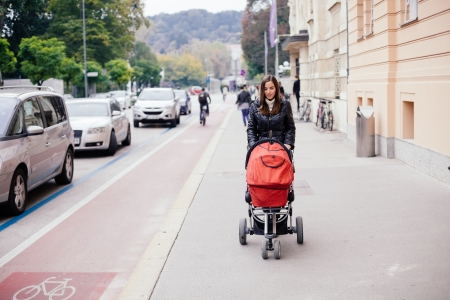 Young woman pushing her baby in stroller on the street photo