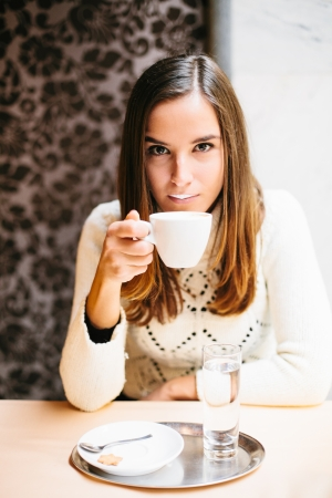 Young woman drinking cappuccino in cafe photo