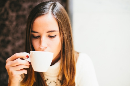 Young woman drinking coffee in cafe photo